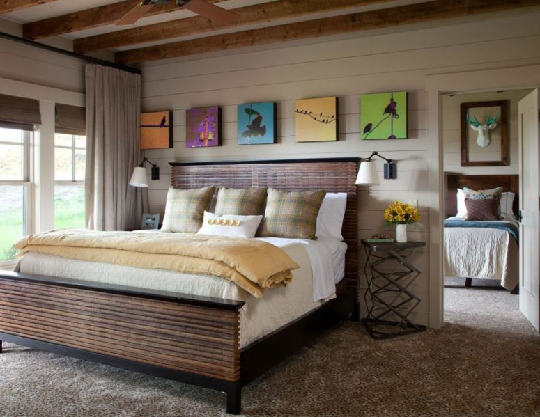 The bedroom is done with a wood slate bed, colorful artworks, metal side tables