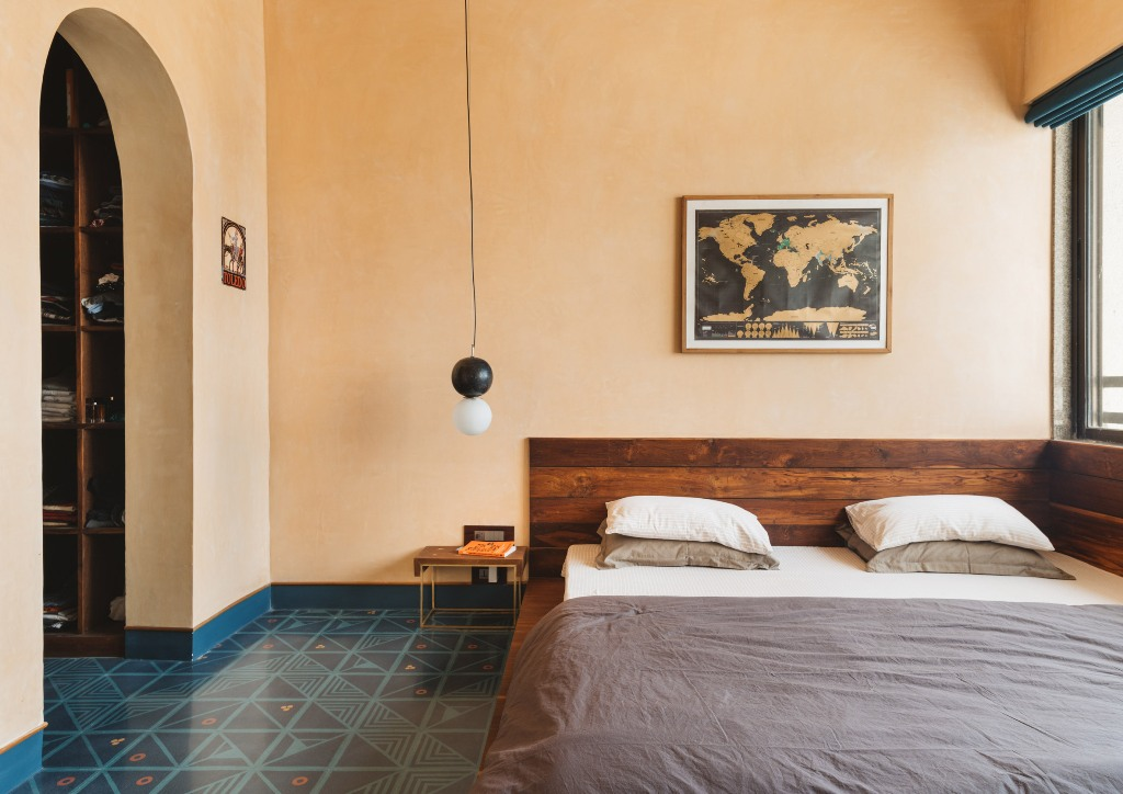 The bedroom is warmer, there's a rich stained wooden bed, a tile floor and lamps