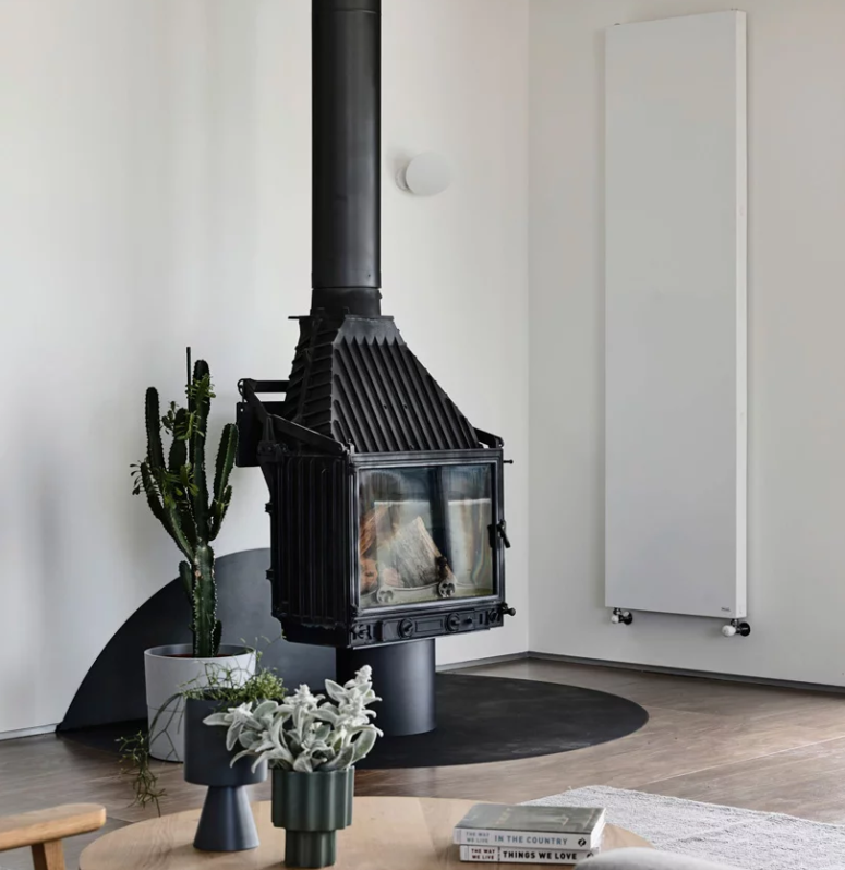 There's a large vintage hearth in black that makes a statement in the space and potted greenery and succulents