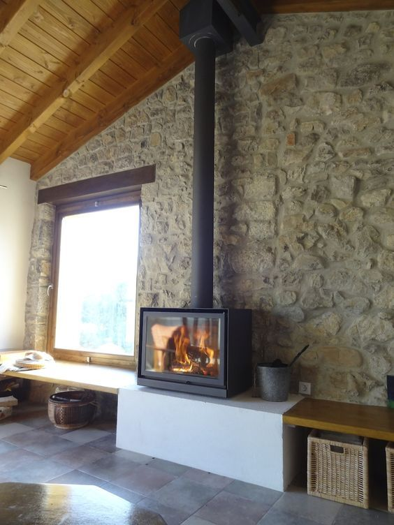 a modern rustic space with stone walls and a wooden ceiling plus a super modern and sleek wood burning stove