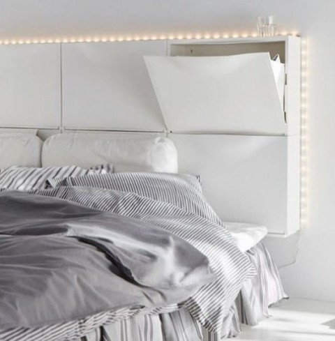 six white IKEA TRONES shoe cabinets are used to create a headboard with much storage