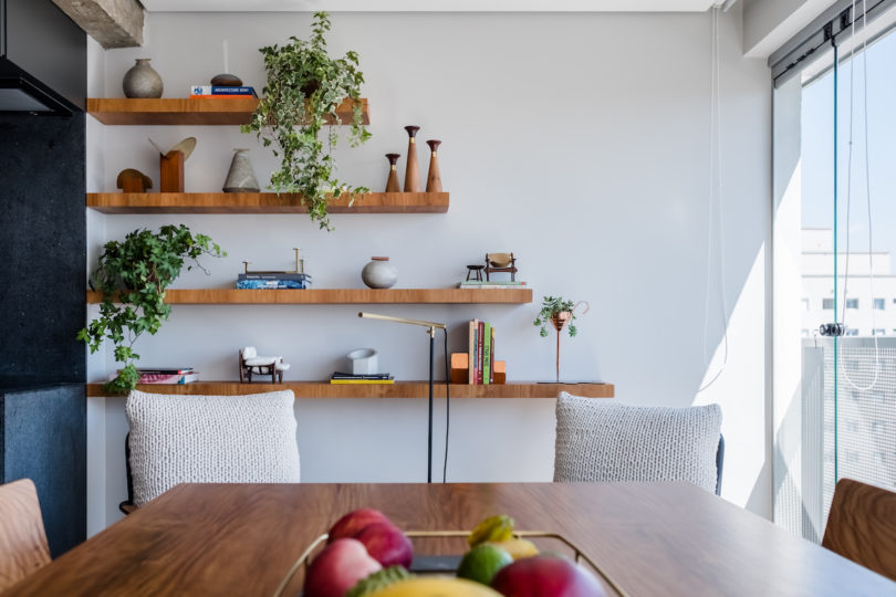 Open shelving paired with crochet covered chairs make the dwelling feel relaxed and boho like