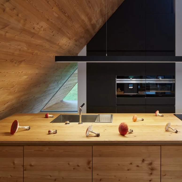 The kitchen features black cabinets, a wooden kitchen island and a simple long lamp to illuminate the space