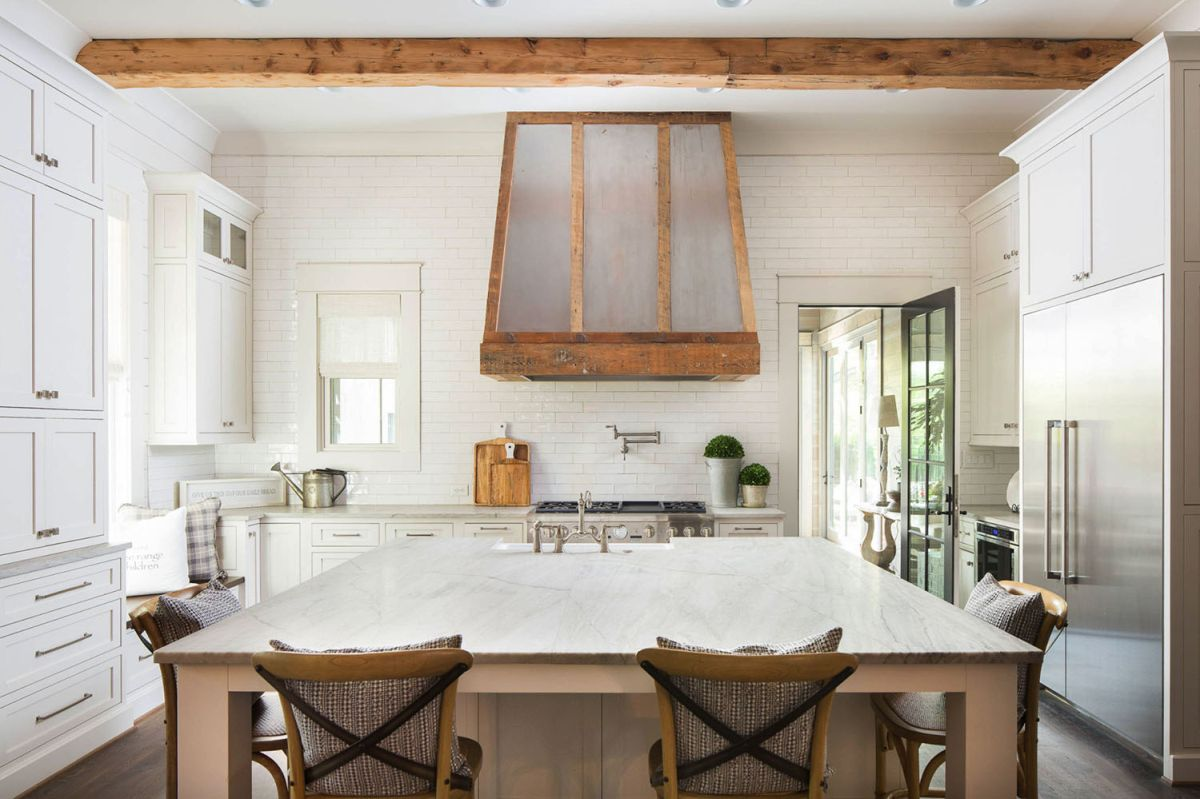 The kitchen is done with neutral cabinets, there's a large kitchen island and table in one
