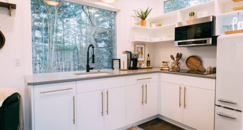 The kitchen is done with white cabinets with gold handles, there's a window to enjoy the views