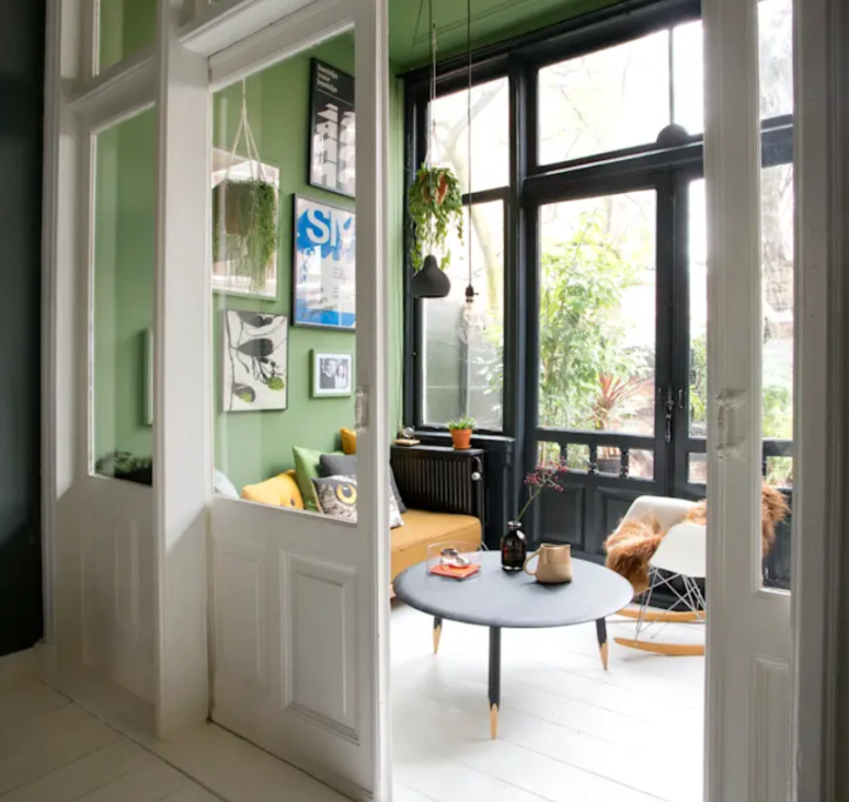 There's a sunroom with bright green walls, a glazed wall, pendant lamps and plants and some cool furniture