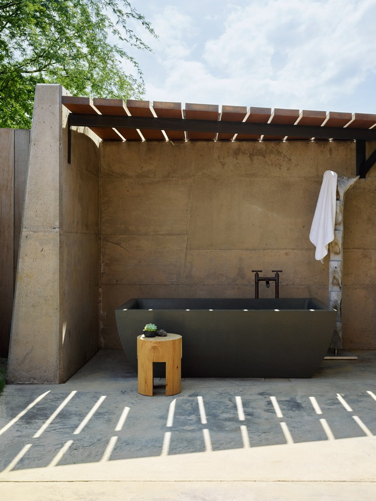 There's an outdoor bathroom with a blakc stone tub, wooden furniture and some greenery
