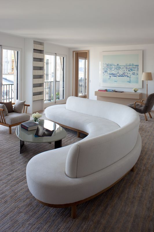 a gorgeous curved white sofa takes over the whole living room and adds soft lines and shapes to it