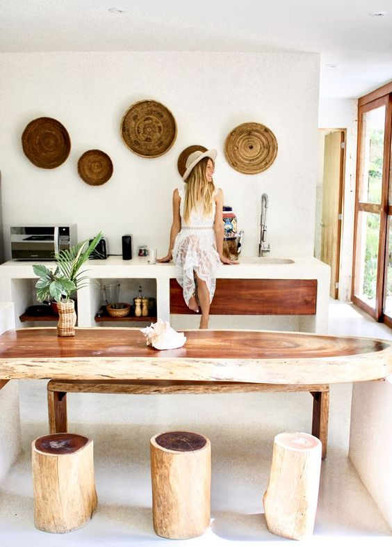 a surf-shaped console table, tree stumps as stools and woven plates on the wall