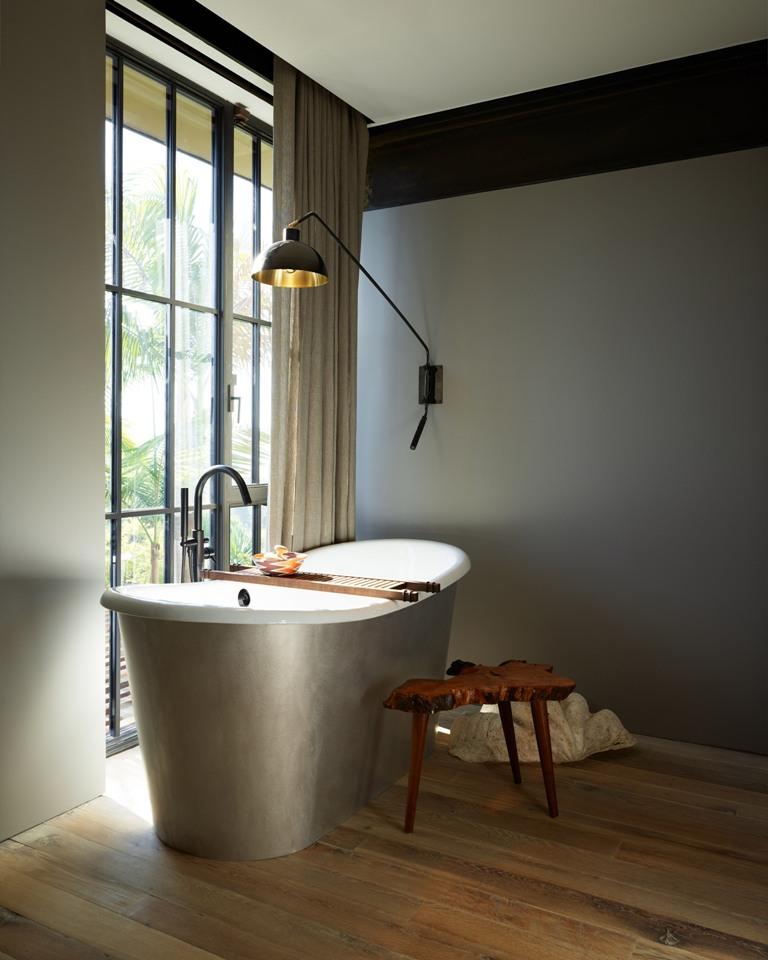 The bathroom is clean and features a full height window with a curtain, a silver oval tub and a catchy wall lamp