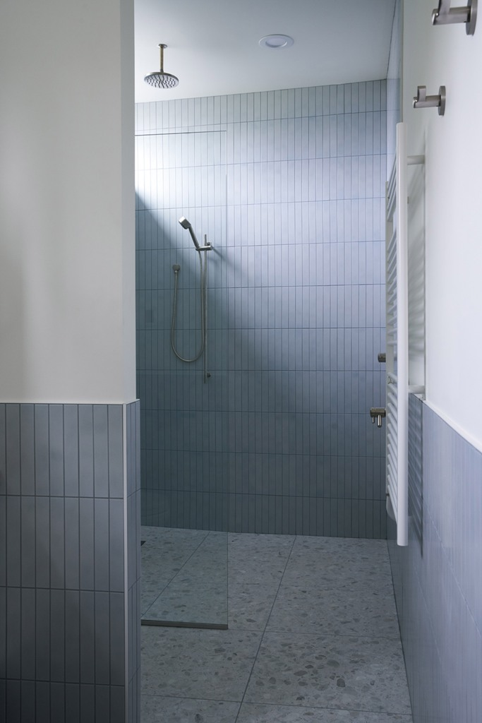 The bathroom is grey amd whoite, with long and thin tiles and a terrazzo floor