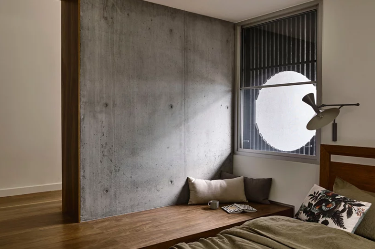 The bedroom features a bed and a platform that shapes a wooden daybed, a window made round with a bamboo screen