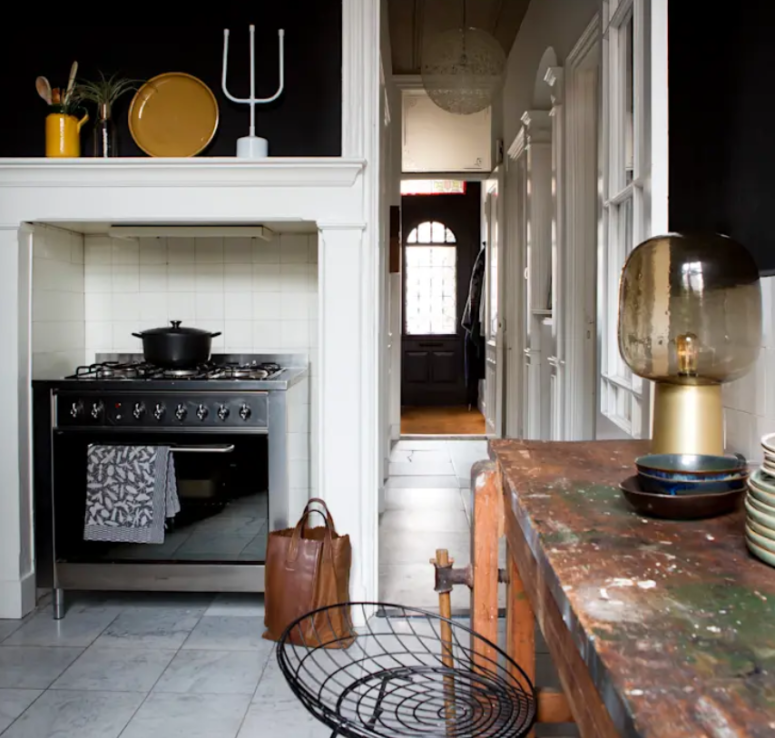 The kitchen features a modern cooker, black walls and white tiles, a shabby chic table and some quirky art and lamps