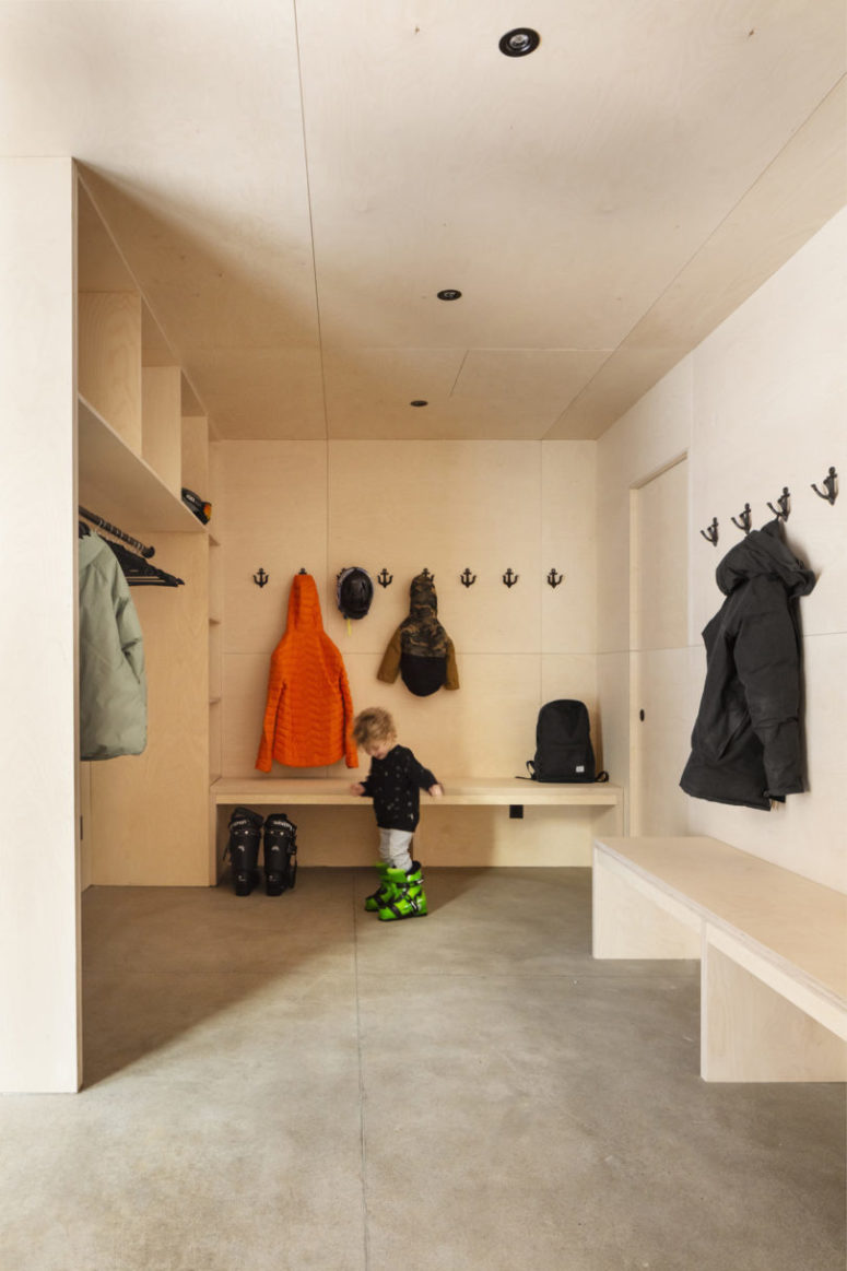 The mudroom is clad with light-colored plywood, all the furniture is made of the same plywood