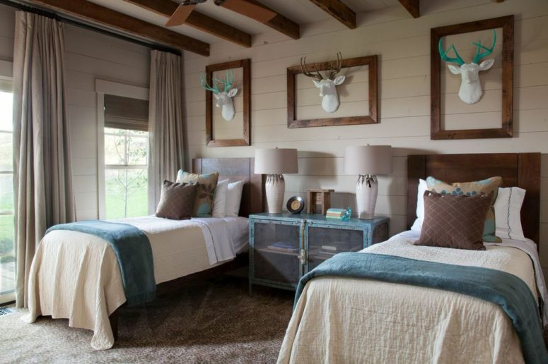 This guest bedroom is done with a blue credenza with sheer doors, catchy fake deer heads and matching beds