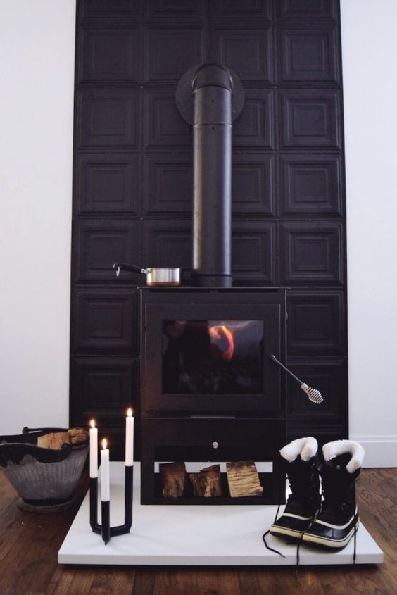 a black modern stove with a black panel wall behind it and a modern candelabra for a bold look