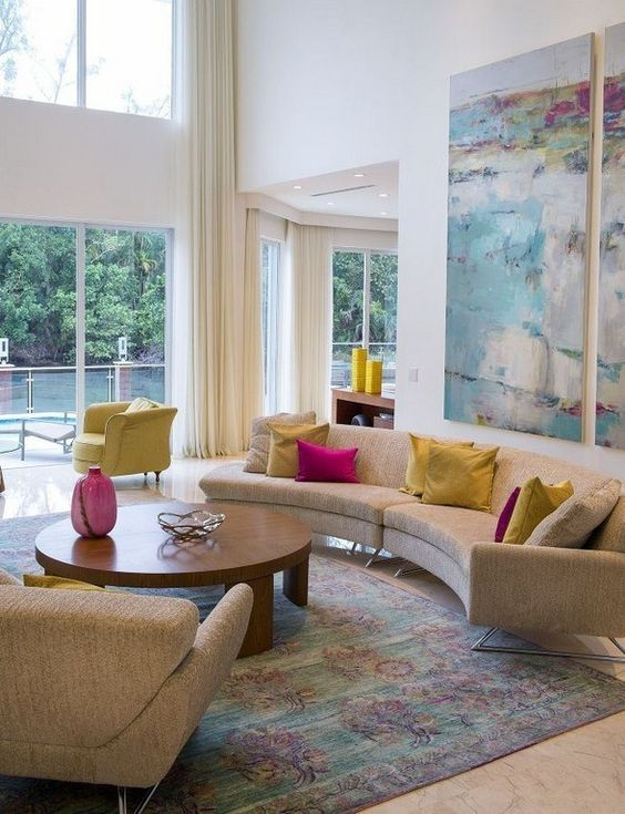 a mid-century modern living room with a curved sofa, colorful pillows and a watercolor artwork for more color