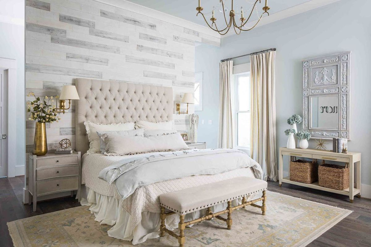 The bedroom is elegant and refined, with an accent wall, chic furniture and an ornate mirror
