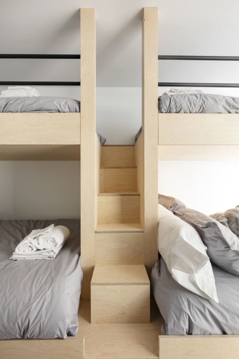 The guest bedroom features four bunk beds, everything is clad with light-colored plywood, too