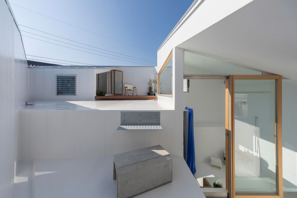 The terrace is done in white, with concrete, some wood and potted greenery