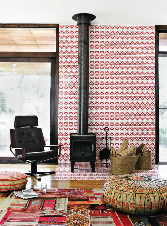 a bold mid-century modern space with a wood burning stove, a bright tiled wall and colorful rugs