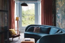 08 a moody and bold living room with a curved blue sofa, orange textiles and moody bird print wallpaper on one wall