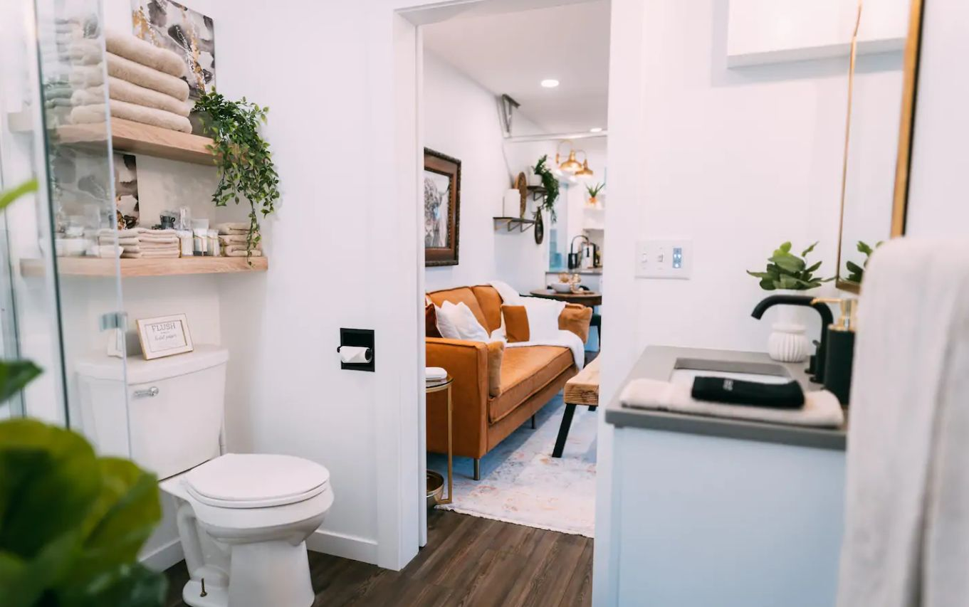 The bathroom is small yet functional, there's open shelving, a shower space and a sink