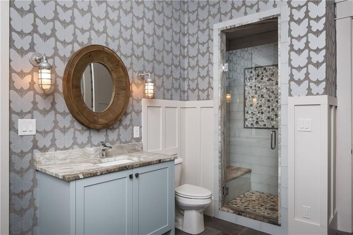 This bathroom is done with butterfly wallpaper, a wood frame mirror and a vanity with a stone countertop