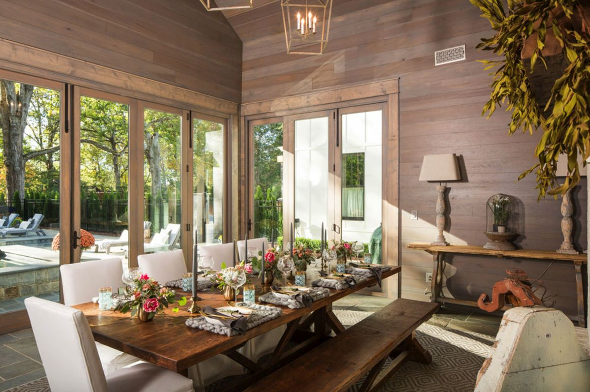 The dining room is clad with dark wood, stained dining set and glazed walls