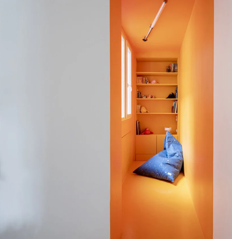 There's a kids' reading nook with bright plywood walls and built-in shelves