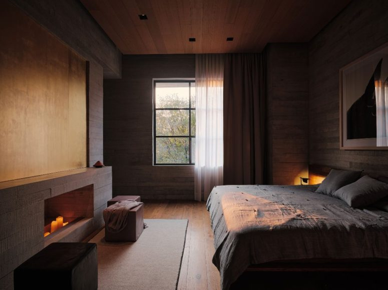 This bedroom features lots of wood, a large bed and a window, a non-working fireplace with candles
