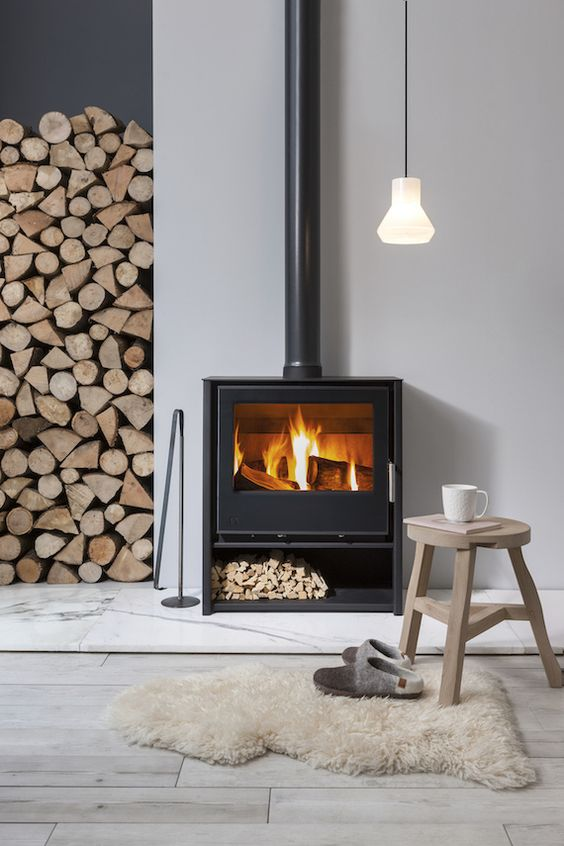 a contemproary space with a Nordic feel is cozied up with a modern wood burning stove and some firewood stored right here
