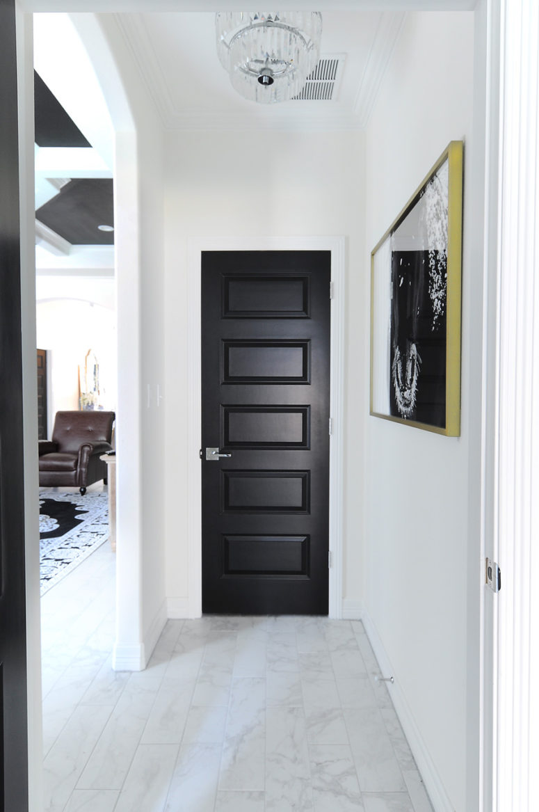 a simple builder grade door can become a real stylish piece if you just paint it matte black like here