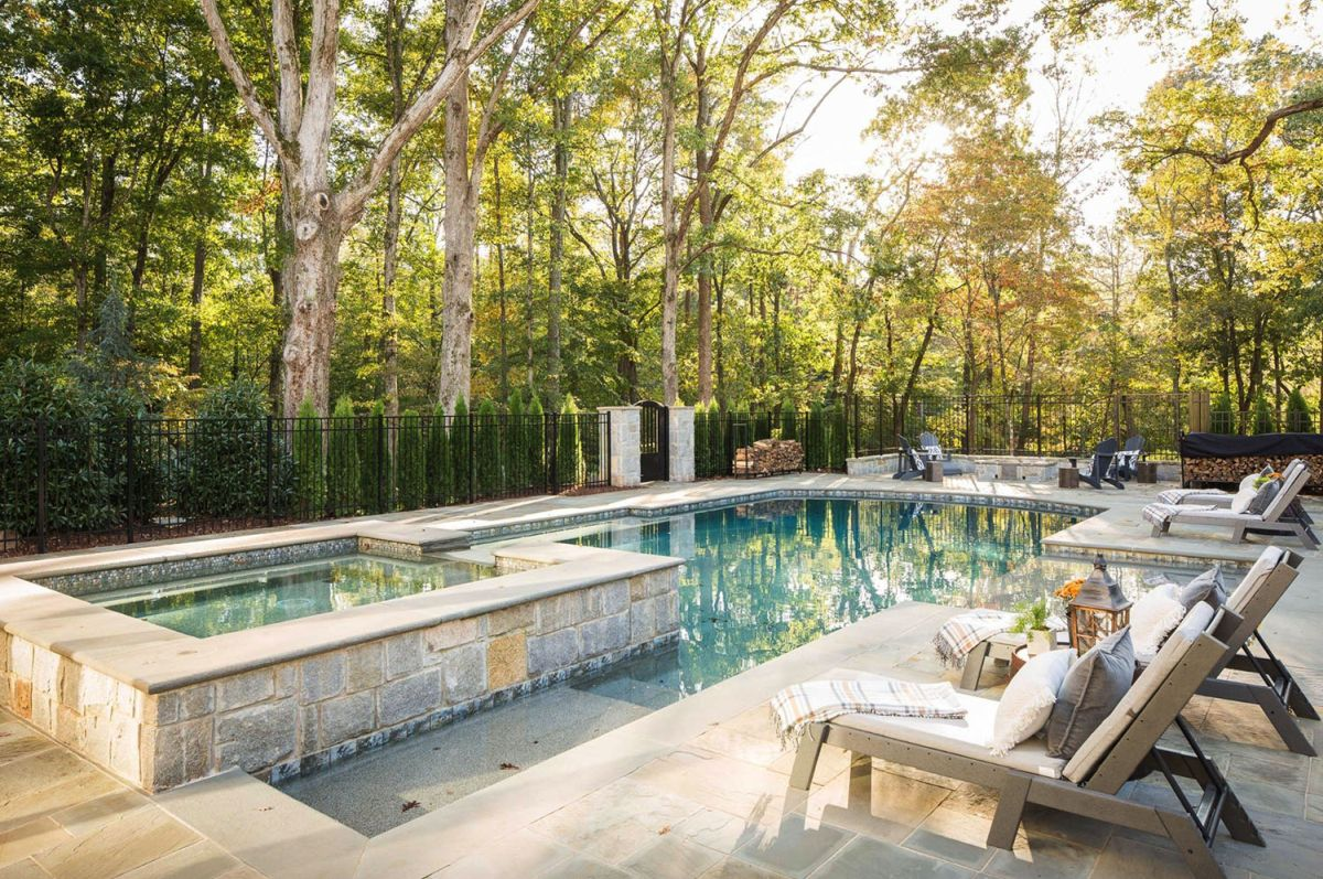 This is a pool zone, the pool is clad with stone and there are wooden chairs