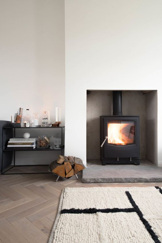 a minimalist space with a white sleek niche with a small modern wood burning stove is a cool idea