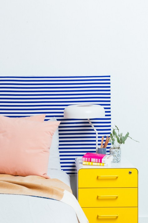 an IKEA Ryggestad table top turned into a colorful headboard with striped fabric