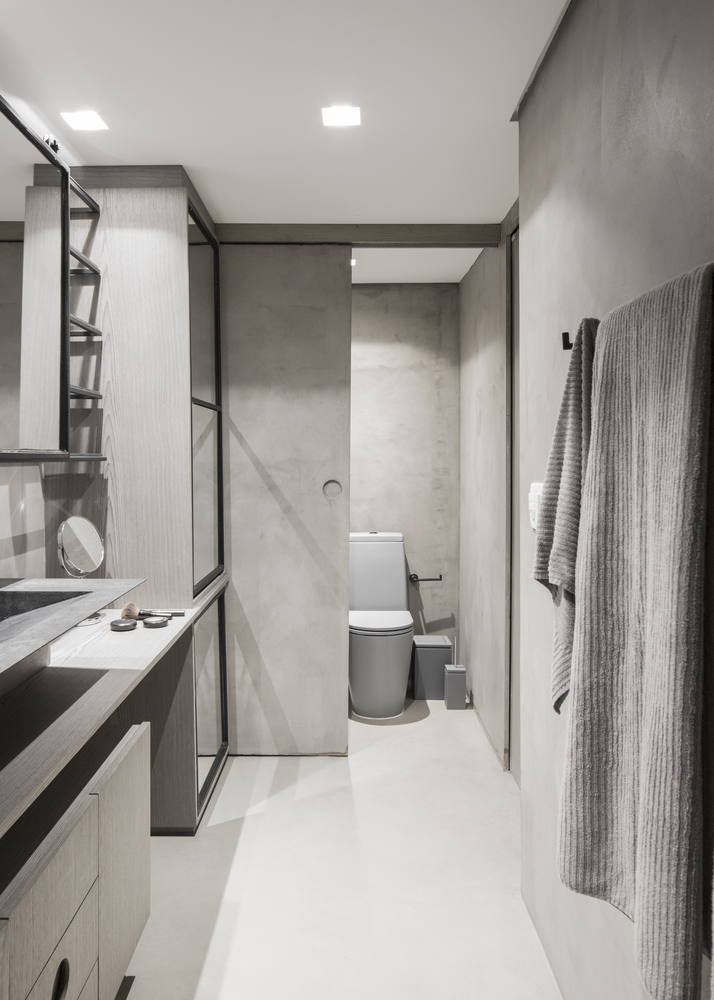 The second bathroom is neutral, fully done in sleek plywood, with mirrors and sliding doors