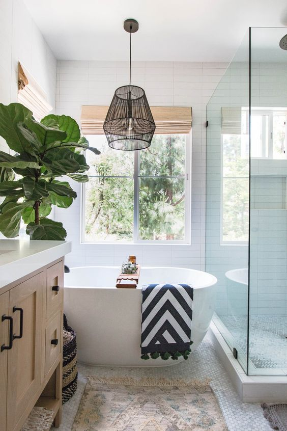 a printed rug and a catchy striped towel make the bathroom feel more californian together with an indoor tree