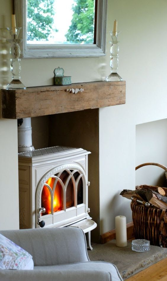 a vintage white wood-burning stove placed into a niche and with a mantel to remind of a classic stove