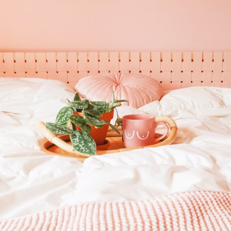 an IKEA Malm headboard hacked with blush fabric that is woven over the existing piece