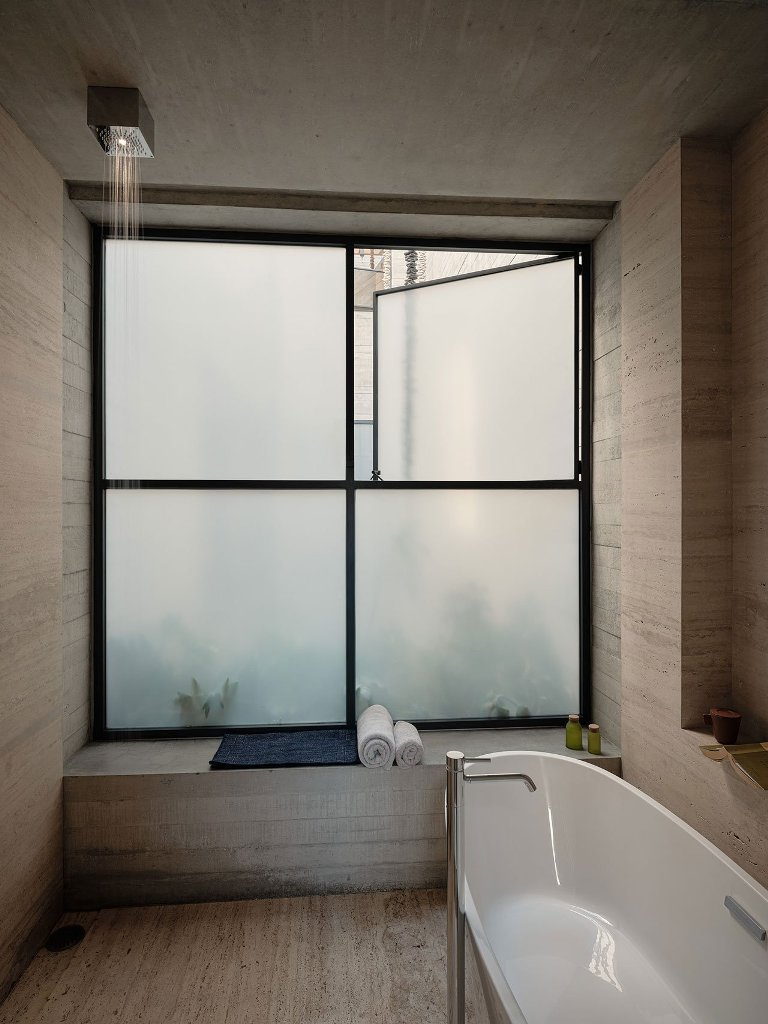 The bathroom is done with a frosted glass window, an oval tub and simple yet luxurious items