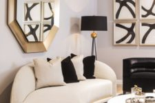 13 a refined space with a curved white and black sofa, gold touches and bold artworks is an amazing living room