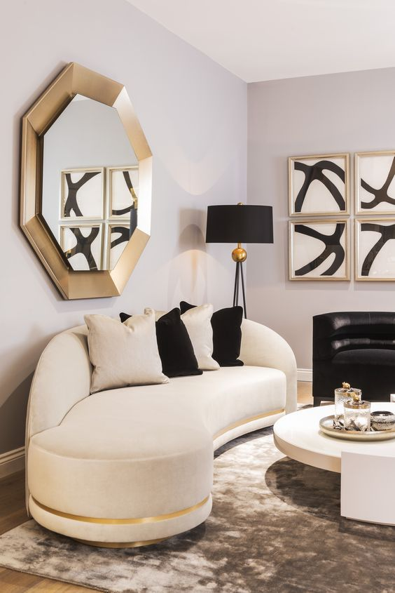 a refined space with a curved white and black sofa, gold touches and bold artworks is an amazing living room