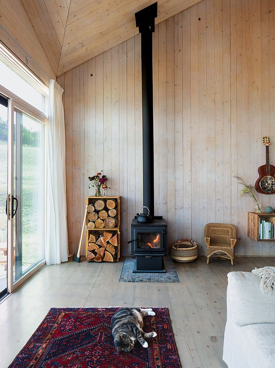 a cabin space fully clad with wood, with a wood burning stove and some firewood in crates for a cozy feel