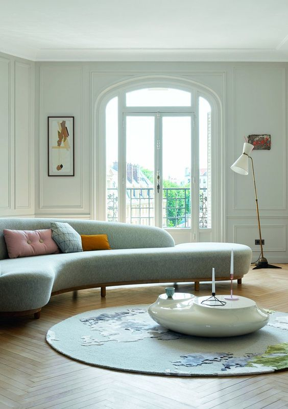 an ethereal living room with a curved blue sofa, an abstract rug and a white pebble coffee table