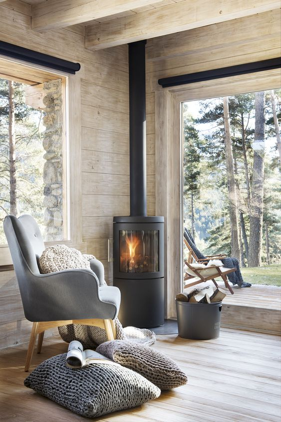 a contemporary cabin space with large windows, wood clad space and a modern wood burning stove in the corner