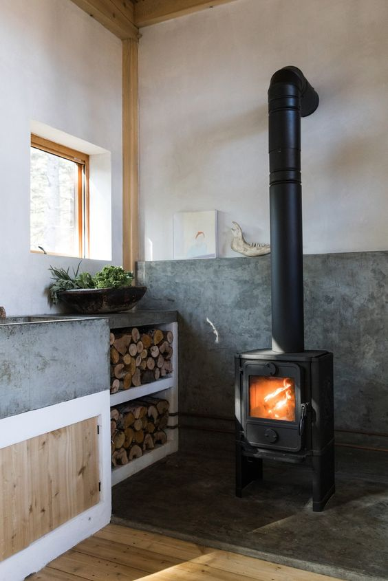 a contemporary kitchen with much concrete in decor and a vintage wood burning stove plus firewood storage