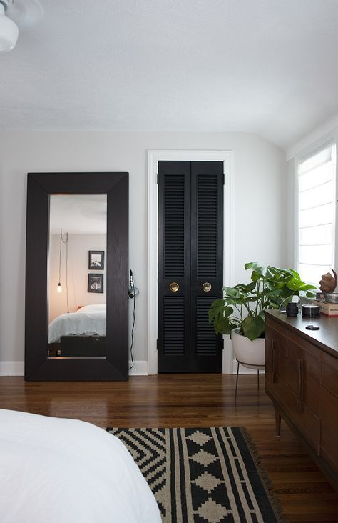 a black shutter door to the closet echoes with a dark wooden frame of the mirror and a printed rug