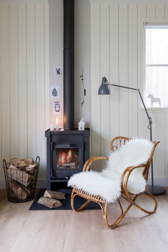 a cozy Nordic nook with wood clad walls and a black wood burning stove plus a wire basket with firewood