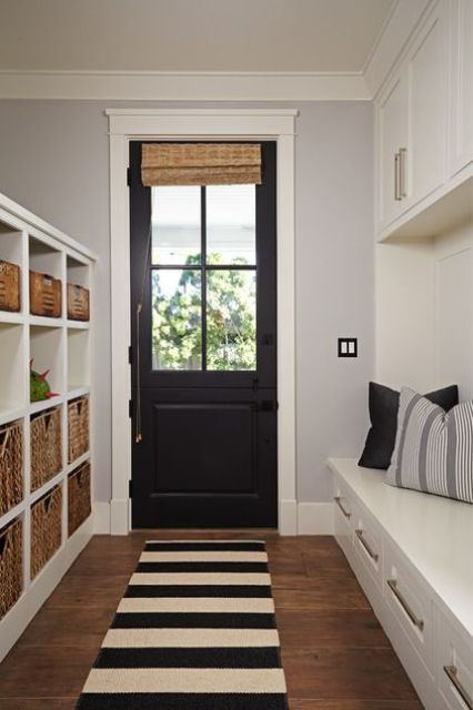 a black door echoes with a striped rug and throws of the mudroom adding a chic and bold touch to the space